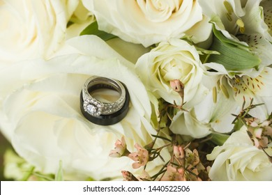 Close up macro of bridal diamond wedding band and engagement ring, and grooms band placed in brides floral bouquet