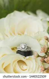 Close up macro of bridal diamond wedding band, grooms band, and engagement ring placed in brides floral bouquet