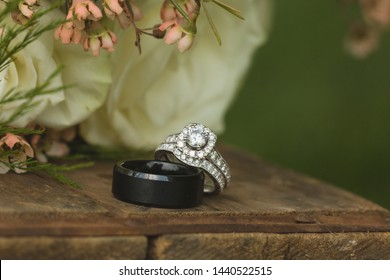 Close up macro of bridal diamond wedding band and engagement ring placed by brides floral bouquet