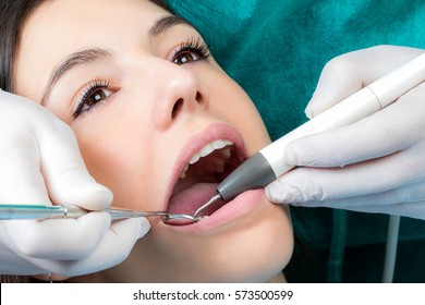 Close up macro face shot of girl at dental check up.Dental hygienist cleaning girls teeth with air scaler and mouth mirror.