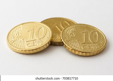 Close up macro of front side of a small pile of three unorganized clean and polished European ten / 10 cent coins on white high quality fibre paper