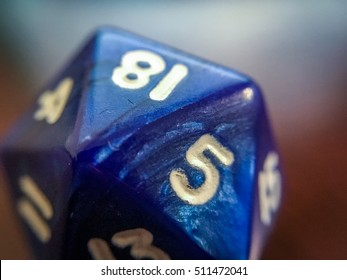 Close Up Macro Photo of a Blue Twenty Sided Role Playing Die - with Visible Scuffs and Scratches on the Surface
