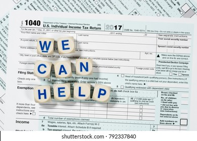 Close macro photo of USA IRS tax form 1040 for year 2017 taken from above with WE CAN HELP spelled out in letters on the form