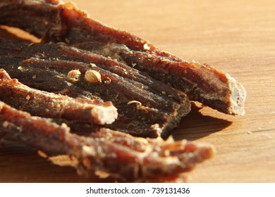 a close up macro shot of biltong (dried meat) on a wooden board. This is a popular South African food snack. This image has selective focusing.