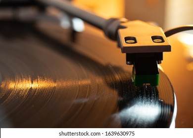 A close up macro shot of the needle through the grooves of a record on a turntable.