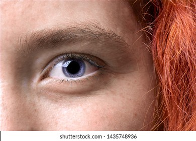 Close up macro shot of a red haired girl eye with freckles