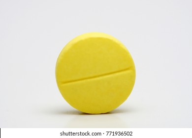 Close up or macro shots of yellow tablet over white background.