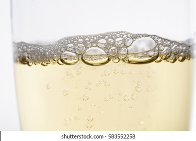 Close up (macro) of sparkling champagne flute style glass, with rising bubbles topped by layer of froth.