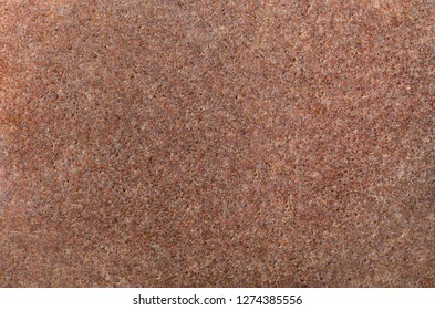 Close up (macro) of stone texture in brown and pink hues.
