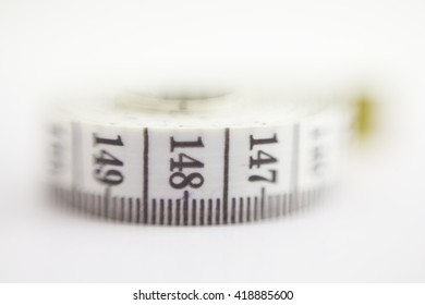 Close up macro view of a curved measuring tape. Measuring tape of the tailor. Closeup view of white measuring tape. Selective focus on a number distance.