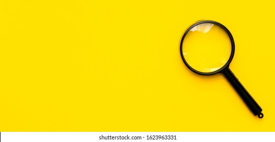 Close up magnifier glass on yellow background. View from above.