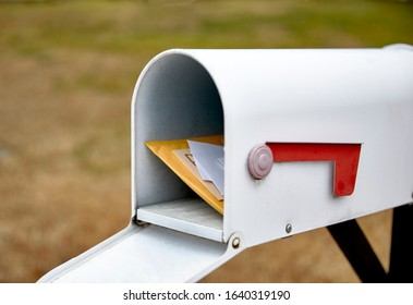 Close up of a mailbox opened with the contents of the mailbox showing with shallow depth of field