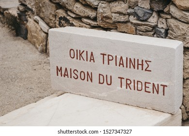 """Close up of the Maison du Trident (""""House of the Trident"""") sign in the theater quarter on the island of Delos, Greece, an archaeological site near Mykonos in the Aegean Sea Cyclades archipelago."""