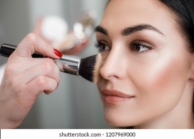 Close up of makeup artist applying light layer of matting powder while using professional brush for lady