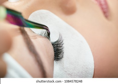 Close up of making lashes with tweezers. Woman's lashes extension. Professional wearing pink hygienic gloves. Using special cosmetic face stickers. Young, healthy skin.