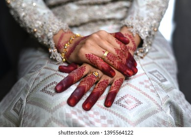 close up of a malay bride hand with henna tattoo and gold rings her wedding day.bride wearing songket fabric, malay tradition dress. Concept of tradition and culture