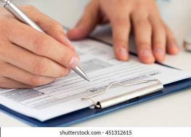 Close up of male accountant filling tax form. Man writing something sitting at his office. Filling individual income tax return form 1040, making financial report, home finances or economy concept