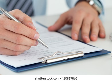 Close up of male accountant making calculations. Man writing something sitting at his office. Making financial report, home finances or economy concept