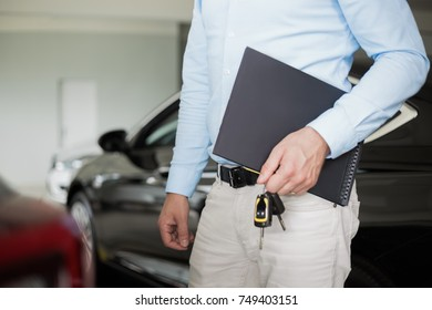 Close up of male adult car dealer standing indoors at car dealership, holding a folder and car keys in his hand with a new car behind him