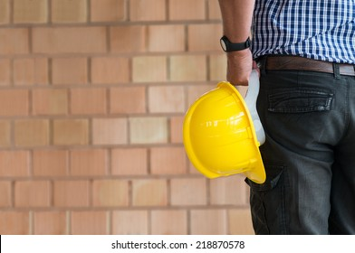 Close up Of Male Architect Holding Yellow Helmet At Construction Site