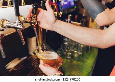 Close up of a male bartender dispensing draught beer in a pub holding a large glass tankard under a spigot attachment on a stainless steel keg.