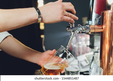 Close up of a male bartender dispensing draught beer in a pub holding large glass tankard under a spigot attachment on a stainless steel keg.