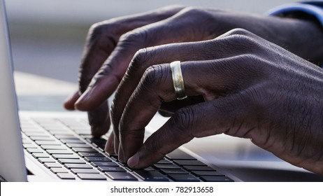 Close up of male black hands typing on a keyboard laptop