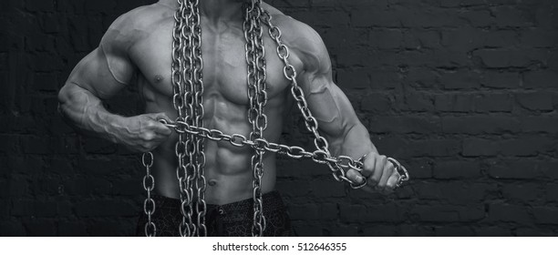 Close up - male body. Strong muscular man breaks the chains on his body.