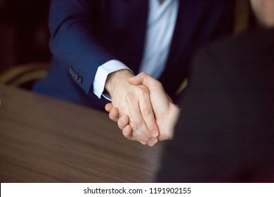 Close up of male business partners shake hands after successful negotiation or meeting in office, employees handshake greeting making good first impression, boss congratulating with promotion