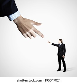 Close up of male businessman pointing at miniature of man