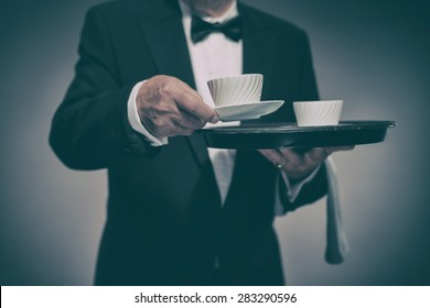 Close Up of Male Butler Wearing Formal Suit and Bow Tie Carrying Tray of White Coffee Mugs and Serving Cup Towards Camera