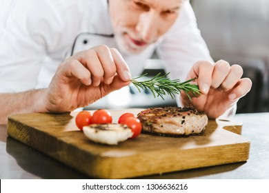 close up of male chef in uniform decorating meat steak with rosemary in restaurant kitchen