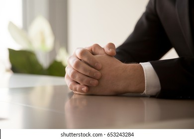 Close up of male clasped hands clenched together on table, businessman preparing for job interview, concentrating before important negotiations, thinking or making decision, business concept