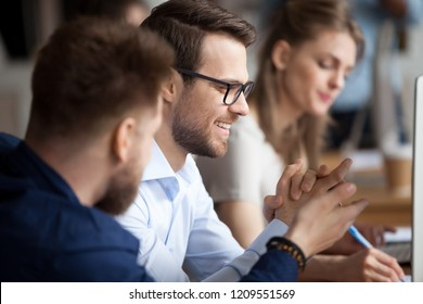 Close up of male colleagues cooperating in coworking office space talking laughing together, smiling man workers chat at workplace, discussing something having fun, employees joke while working at pc