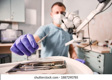 Close up of male dentist hand in sterile glove holding metal dental explorer. Stomatologist in medical mask taking dental instrument while sitting near diagnostic microscope. Concept of dentistry.