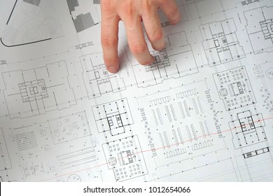 Project drawings human hands drawing house stock photo edit now close up of male design engineer sits at the desk in her office blueprints laying malvernweather Choice Image