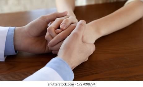 Close up of male doctor hold female patient hands show empathy and support at consultation in hospital, caring man physician comfort upset woman client, help with bad checkup results news in clinic