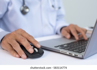 Close up of male doctor working on laptop computer on white desk in hospital, electronic health records system EHRs, electronic medical records system EMRs, telemedicine concept, selective focus.