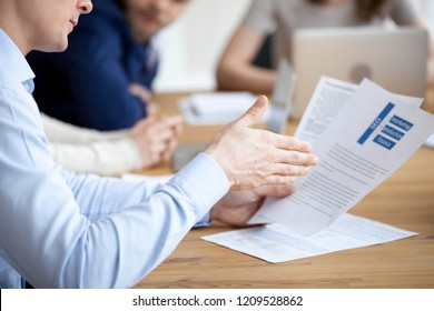 Close up of male employee read paper handout material during office meeting, man analyzing paperwork report at briefing, explaining content to colleague, worker sit at desk looking through document