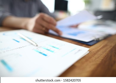 Close up of male employee read paper handout material during office meeting, man analyzing paperwork report at briefing.