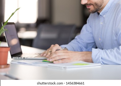 Close up of male employee sit at office desk analyzing statistics making financial notes working on laptop online, focused man worker writing important data considering business plan using computer
