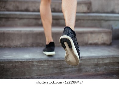 Close up of male feet in sneakers walking up the stairs. Athlete man legs running up