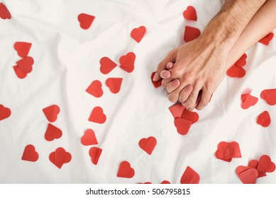 Close up of male and female arms on bed with small paper hearts. Loving couple is holding hands
