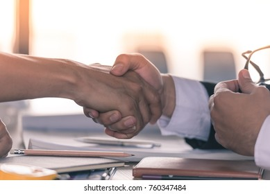 Close up of male and female business people shaking hands as a sign of agreement on the talbe, partners, commitment concept.