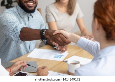 Close up male and female diverse business people handshake during negotiating and signing contract. Group of partners at multiracial meeting gathered together for startup discussion or trade details