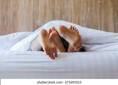 Close up of male and female feet on a white bed. The concept of loving couple having sex under white sheets in the bedroom. Sensual and intimate moment of lovers. Focus on male foot.