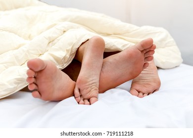 Close up of male and female feet sleeping side by side in bed, Moment of lovers concept