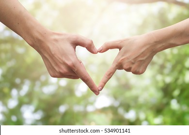close up male and female hands making heart on blurred bokeh nature backgrounds for lover fall in love concept.