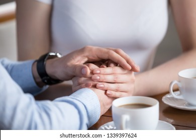 Close up of male and female hands. Millennial couple gently holding each other with hands. Young pair having romantic breakfast. Helping, taking care, trust in marriage, love and support concept
