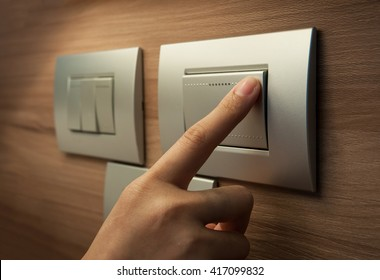 Close up of male finger is turn off on grey button of light switch over wood wall at home. Power, Energy, Saving Electrical.